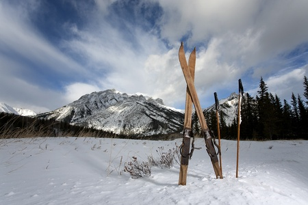 vintage skis in snow with mountains and clouds in the background Reklamní fotografie