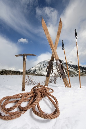 ice axe: vintage skis, ice axe and rope in snow with winter scenery background Stock Photo
