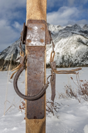 vintage ski bindings closeup with winter scenery in background