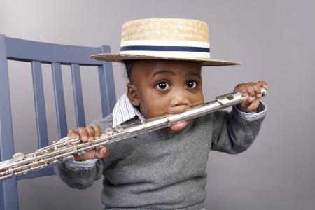 flauta: muchacho ni�o sosteniendo una flauta en la boca Foto de archivo
