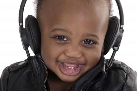 portrait of a smiling very young child with headphones wearing leather jacket photo