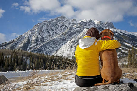 woman and her dog admiring the view sitting on a rock facing the mountains in the background