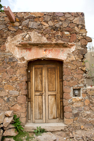 run down: old wooden door on a run down stone house