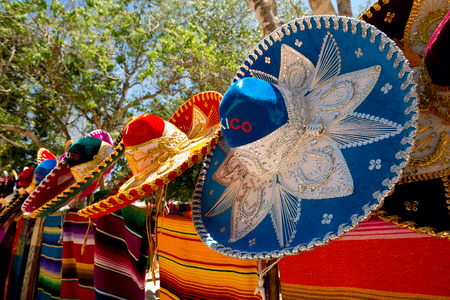 colorful Mexican sombreros and ponchos lined up outdoors 스톡 콘텐츠