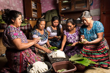 specific: January 20, 2015, San Pedro la Laguna, Guatemala: traditionally dressed mayan tzutujil women preparing specific local food on the house floor
