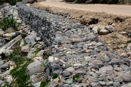 retaining: mesh and rock retaining wall built along road construction in Honduras