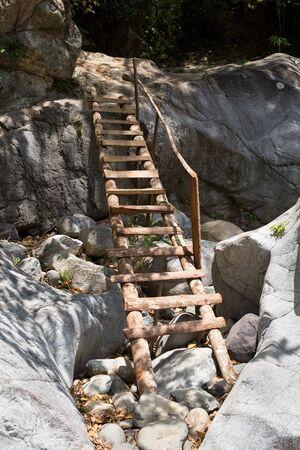 decent: wooden access ladder built on side of rock cliff