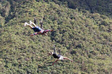 July 15, 2016 Banos, Ecuador: two men slide head first on zipline across a canyon