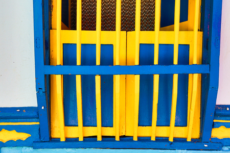 building exteriors: wooden colourful colombian window security bar closeup