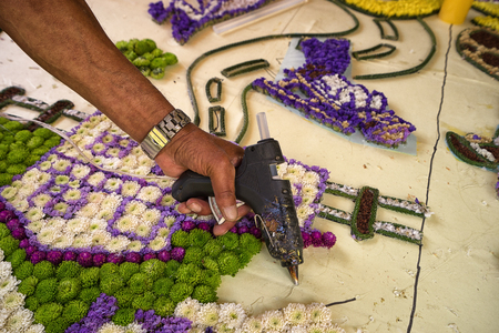 August 6, 2017 Medellin, Colombia: a farmer is gluing flowers one by one with hot glue to a large panel which will be presented at the flower festival parade Redakční