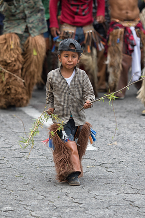 June 29, 2017 Cotacachi, Ecuador: kichwa indigenous child with chaps dancing on the street during Inti Raymi festival
