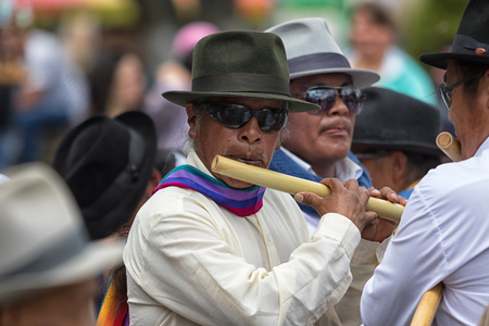 June 29, 2017 Cotacachi, Ecuador: indigenous kichwa man playing a flute made of bamboo during summer solstice celebrations