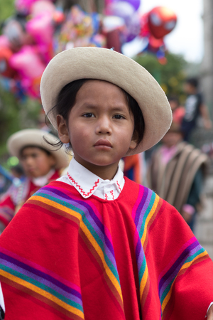 June 18, 2017 Pujili, Ecuador: closeup of a young indigenous young kichwa boy wearing a colourful traditional dress at Corpus Christi parade