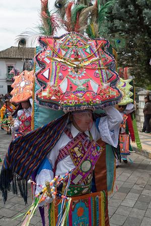 June 18, 2017 Pujili, Ecuador: indigenous kichwa man in colourful costume balancing a large display on his head at Corpus Christi parade