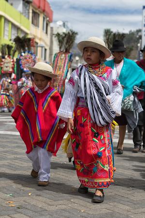 June 18, 2017 Pujili, Ecuador: indigenous kichwa girl and boy walking at the Corpus Christi parade