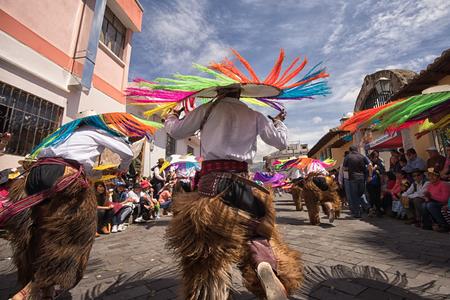 June 17, 2017 Pujili, Ecuador: male indigenous dancers in chaps wearig large hats dancing in the street at Corpus Christi parade