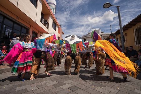 June 17, 2017 Pujili, Ecuador: dancers in brightly colored costumes  performing on the street during Corpus Christi parade