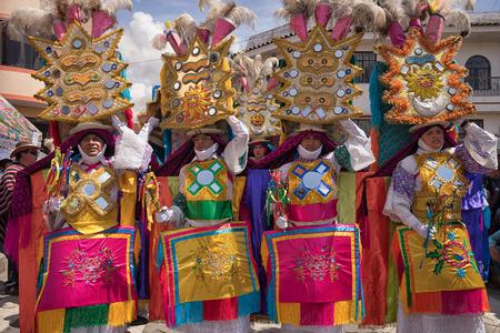 2017 년 6 월 17 일 Pujili, 에콰도르 : 코퍼스 크리스티 퍼레이드에서 남성 댄서들이 착용하는 무겁고 정교한 밝은 색 머리 장식