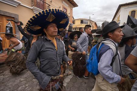 June 24, 2017 Cotacachi, Ecuador:  indigenous kichwa men     wearing chaps dancing in the street at the Inti Raymi parade at summer solstice Editorial