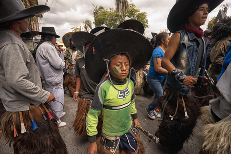 June 24, 2017 Cotacachi, Ecuador:  indigenous kichwa boy wearing chaps dancing in the crowd at the Inti Raymi parade at summer solstice Editorial