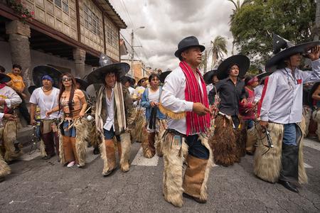 June 24, 2017 Cotacachi, Ecuador:  indigenous kichwa men wearing chaps dancing at the Inti Raymi parade at summer solstice