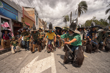 June 24, 2017 Cotacachi, Ecuador:  indigenous kichwa men     wearing chaps dancing in the street at the Inti Raymi parade at summer solstice Editorial