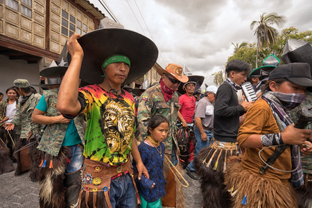 June 24, 2017 Cotacachi, Ecuador:  indigenous kichwa people wearing chaps dancing in the crowd at the Inti Raymi parade at summer solstice Editorial