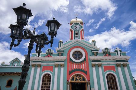 Colorful church facade in the popular tourist destination town in the Andes Vilcabamba, Ecuador. Фото со стока