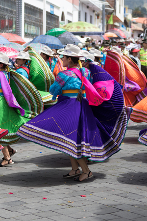 June 17, 2017 Pujili, Ecuador: young female dancers in bright color traditional wear performing on the street at Corpus Christi celebrations Editorial