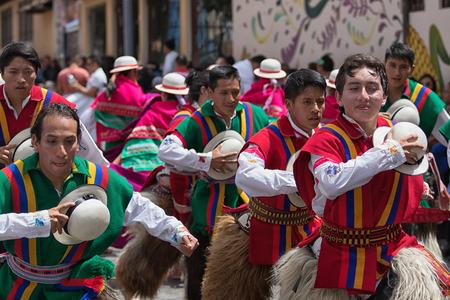 June 17, 2017 Pujili, Ecuador: male dancers holding their hats in the air at Corpus Christi festival