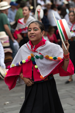 June 17, 2017 Pujili, Ecuador: young kichwa woman in traditional clothing performing street dance at the annual Corpus Christi festival in the Andean town