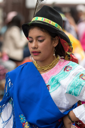 June 17, 2017 Pujili, Ecuador: young indigenous woman in bright color traditional clothing at Corpus Christi parade dancing in the street Editorial