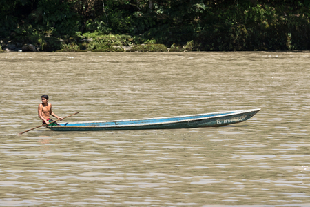 June 6, 2017 Misahualli, Ecuador:  indigenous man in canoe on the Napo river in the Amazon area Stock Photo
