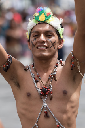 June 17, 2017 Pujili, Ecuador: bare chested indigenous man from the Amazon area dancing in the street at Corpus Christi parade