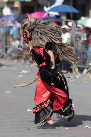 June 17, 2017 Pujili, Ecuador: closeup of a male dancer with colorful traditional face mask at the Corpus Christi annual parade