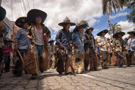 June 25, 2017 Cotacachi, Ecuador: indigenous quechua men wearing sombreros and chaps at the Inti Raymi celebrations