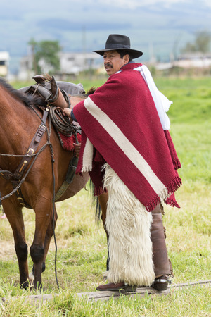 June 3, 2017 Machachi, Ecuador: cowboy from the andes called chagra arranging horse saddle before a rural rodeo