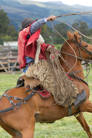 June 3, 2017 Machachi, Ecuador: closeup of indigenous quechua cowboy in motion on horseback  dressed traditionally handling lasso on horseback