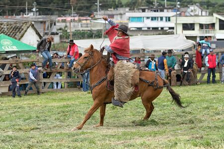 June 3, 2017 Machachi, Ecuador: indigenous quechua cowboy in field dressed traditionally handling lasso on horseback
