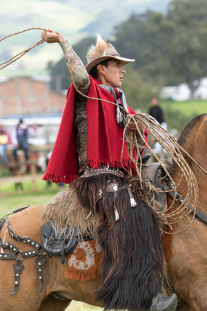 June 3, 2017 Machachi, Ecuador: Andean cowboy on horseback in motion wearing chaps and poncho