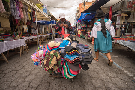 April 29, 2017 Otavalo, Ecuador: mobile vendor selling hats from a cart in the Saturday market Редакционное
