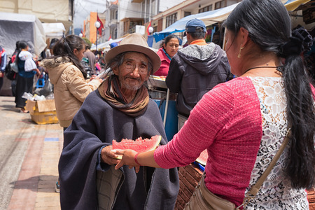May 6, 2017 Otavalo, Ecuador: a woman hands over a slice of watermelon to a poor indigenous man