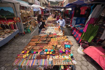 April 29, 2017 Otavalo, Ecuador: indigenous quechua people selling artisan gifts on stands set up on the street in the Saturday market Stock fotó - 90124201
