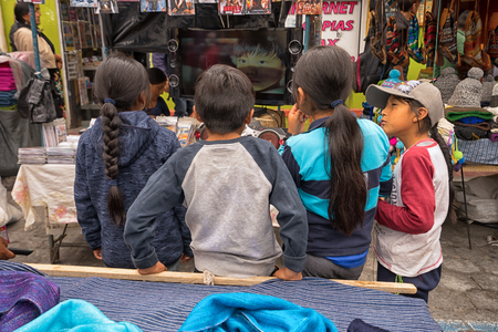 April 29, 2017 Otavalo, Ecuador: indigenous quechua children watching TV on the street in the Saturday market Stock fotó - 90124177
