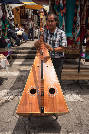 May 6, 2017 Otavalo, Ecuador: indigenous quechua man playing the harp  in the Saturday market Stock fotó - 90124181