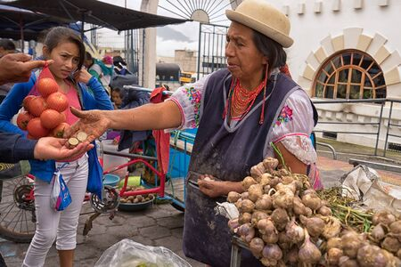 May 6, 2017 Otavalo, Ecuador: produce vendor in the Saturday market giving change to costumer Stock fotó - 90124183