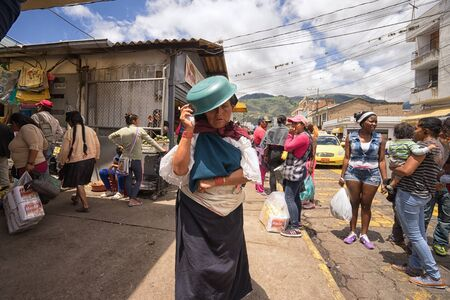 April 13, 2017 Ibarra, Ecuador: a woman walks with plastic bowl on her head as sun protection Editorial