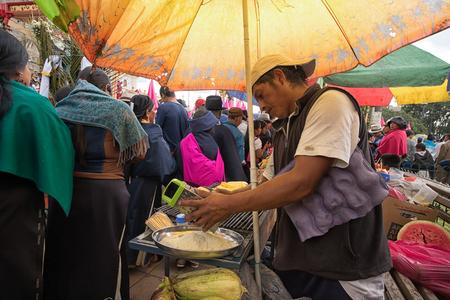 2017 年 4 月 14 日コタカチ、エクアドル: 男はイースター パレードを先住民族 kechwa 群衆の端に foodstand でチーズを格子 報道画像