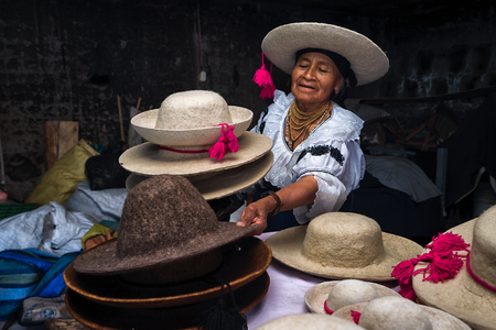 2017 년 4 월 21 일 Iluman, 에콰도르 : 그녀의 상점이 생산하는 다양한 전통적 느낌의 모자를 선물하는 quechua 여성