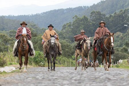 May 27, 2017 Sangolqui, Ecuador: cowboys in traditional wear riding horses on a cobblestone country road towards a rural rodeo